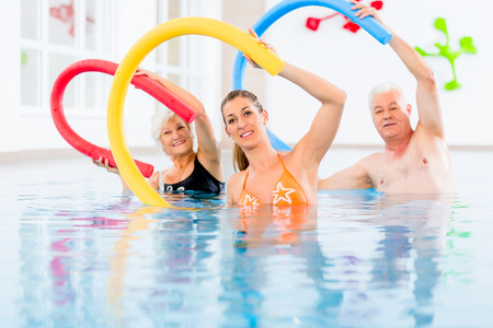 pool water: Group  or young and senior people in aquarobic fitness swimming pool exercising with  pool noodle