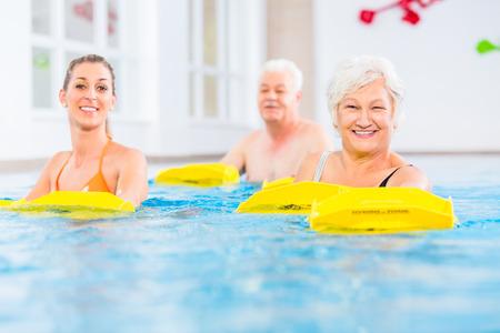 Senior und junge Menschen in Wassergymnastik mit Widerstandseinrichtung Lizenzfreie Bilder