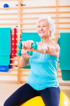 gimnasia: Mujer mayor que hace deporte de fitness en el gimnasio con pesas Foto de archivo