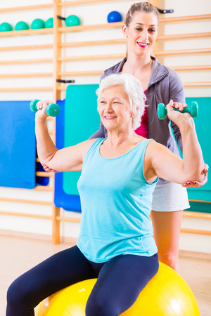 elderly exercise: Senior woman with trainer doing fitness sport in gym Stock Photo