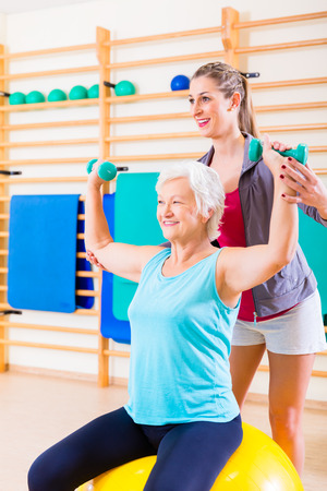 Senior woman with trainer doing fitness sport in gym Stock Photo