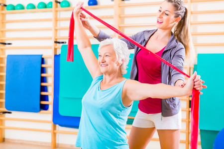 elastic: Senior woman with stretch band in fitness gym being coached by personal trainer