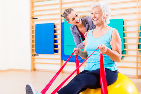 Senior woman with stretch band in fitness gym being coached by personal trainer