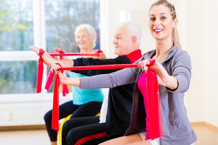 actividad fisica: Personas, j�venes y mayores, en el ejercicio de gimnasio con banda el�stica Foto de archivo