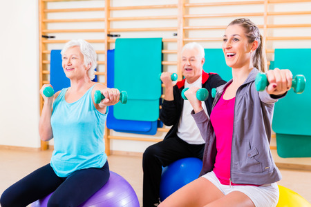 elderly: Group of senior and young people at physiotherapy doing exercises