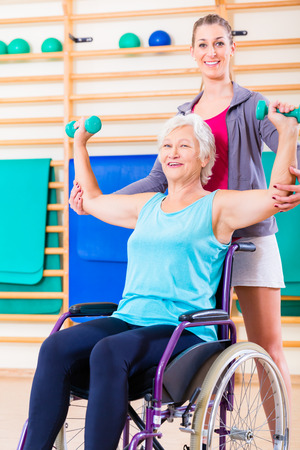 disabled seniors: Senior woman in wheel chair doing physical therapy with her trainer