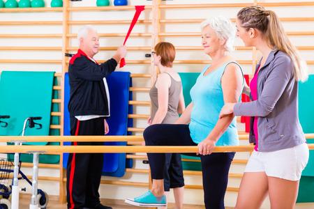 ancianos caminando: Mayores en la terapia de rehabilitaci�n f�sica con el entrenador