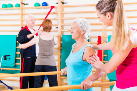 therapies: Seniors in physical rehabilitation therapy with trainer