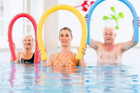 actividad fisica: Grupo o j�venes y personas mayores en aquarobic nataci�n gimnasio piscina ejercitan con piscina fideos Foto de archivo