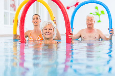 rehabilitation: Group  or young and senior people in aquarobic fitness swimming pool exercising with  pool noodle