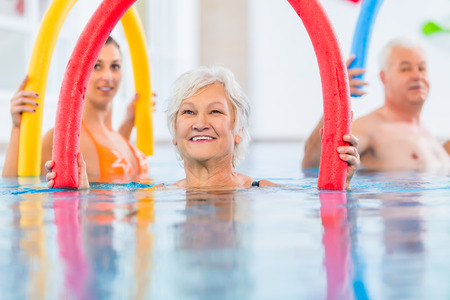 hydrotherapy: Group  or young and senior people in aquarobic fitness swimming pool exercising with  pool noodle