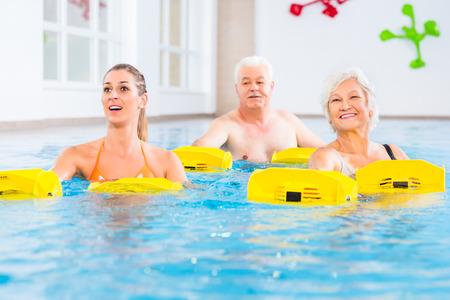 gimnasia: Personas mayores y jovenes en gimnasia en el agua con dispositivo de resistencia