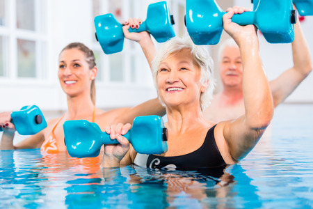 hydrotherapy: People young and senior in water gymnastics physiotherapy with dumbbells