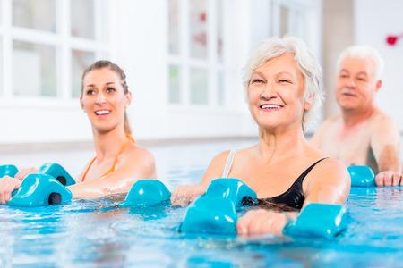 Jungen und älteren Menschen in Wassergymnastik Physiotherapie mit Hanteln