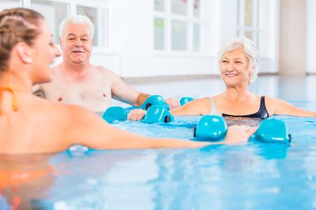 gymnastique: Les personnes jeunes et seniors dans l'eau gymnastique physioth�rapie avec des halt�res Banque d'images