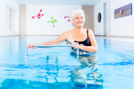 hydrotherapy: Senior woman in underwater gymnastics therapy with sliding machine