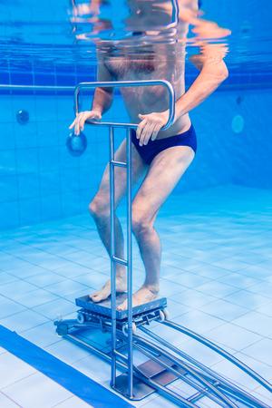 Senior man in underwater gymnastics therapy with sliding machine