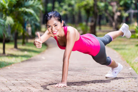 pushup: Proud and successful woman doing sport push-up in tropical Asian park, giving the thumbs up sign during her exercise Stock Photo
