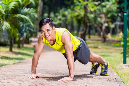 pushup: Strong Asian man doing sport push-up in park looking at camera