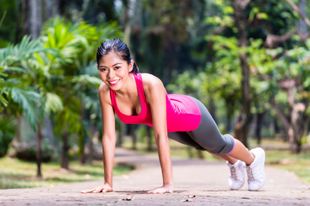 pushup: Proud and successful woman doing sport push-up in tropical Asian park, looking in camera during her exercise Stock Photo