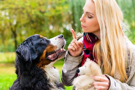 obediencia: Muchacha en parque del otoño entrenar a su perro en obediencia dando la orden de sentado