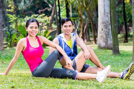 situp: Couple doing sit-up in tropical Asian park, man and woman sitting on the lawn in sport exercise Stock Photo