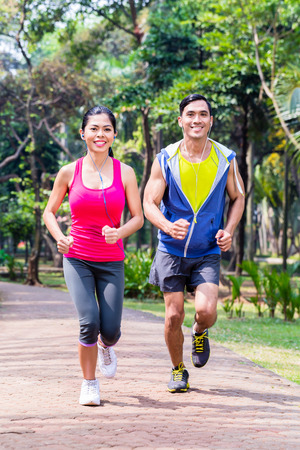 asian boy: Asian couple, man and woman, jogging or running in tropical Asian park for fitness Stock Photo