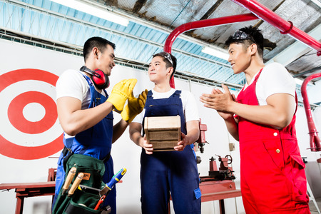 cabinet maker: Team of Asian workers discussing product as a work team