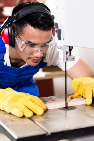 carpintero: Carpintero asiático o trabajador en la sierra cortando madera en el taller Foto de archivo
