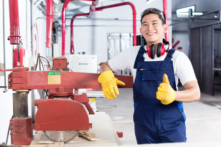 cabinet maker: Proud Asian carpenter showing thumbs up standing next to machine in his workshop