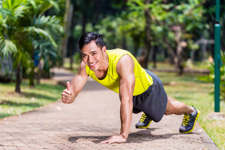 pushup: Proud and successful man doing sport push-up in tropical Asian park giving the thumbs-up sign