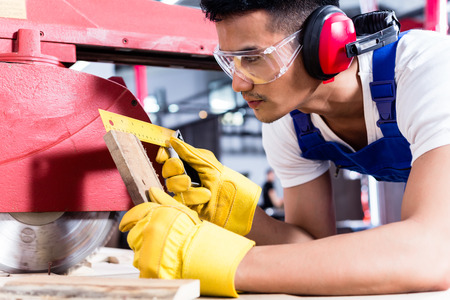 circular saw: Carpenter in Asian workshop with circular saw in a manufacturing factory Stock Photo