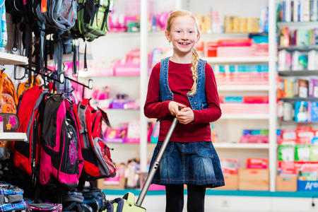 first day of school: Pupil buying supplies and bag for first day in school Stock Photo
