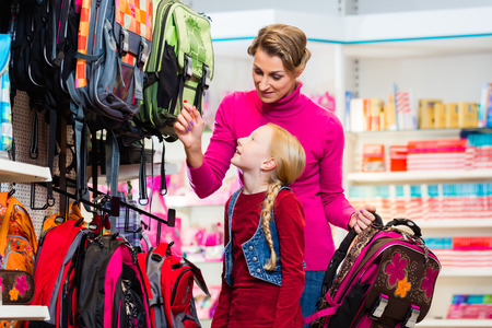 first day of school: Family buying school satchel or bag in store preparing for first day in school