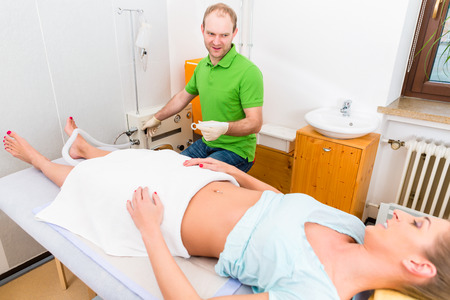 colon cleansing: Woman at colon therapy with alternative practitioner lying on bench in practice