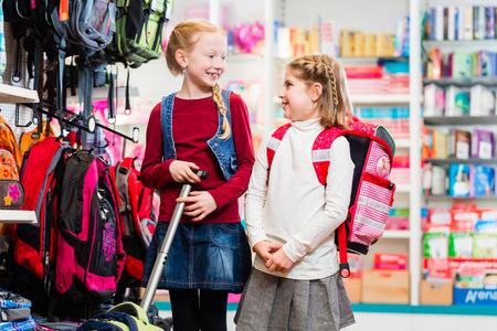 niños de compras: Dos hermanas comprar útiles escolares, mochila y bolsa, en la tienda Foto de archivo