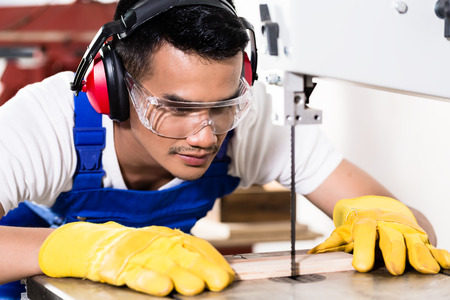 safety goggles: Asian carpenter or worker on saw cutting wood in workshop