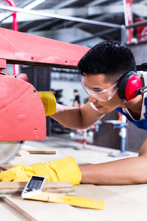 cabinet maker: Carpenter in Asian workshop with circular saw in a manufacturing factory Stock Photo