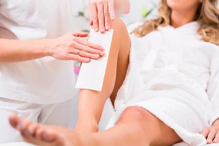 depilacion: Mujer que recibe la depilación con cera para la depilación en salón de belleza