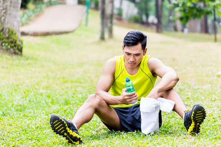tomando agua: Asian man having break from sport training in tropical park, drinking water from a bottle Foto de archivo