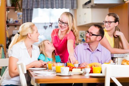 familia comiendo: Familia que desayuna conjunta en la cocina de comer y beber
