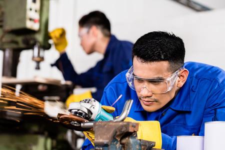 Zwei asiatische Industriearbeiter in der Metallfabrik mit elektrischen Schleifwerkzeug und Bohrmaschine Maschine