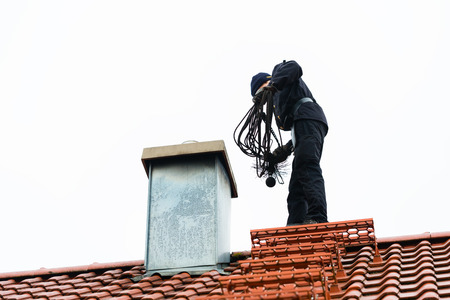 Chimney sweep standing on roof of home working photo