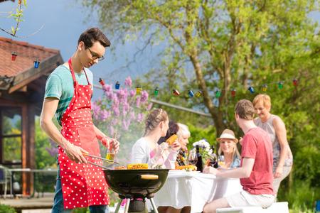 fiesta familiar: Los familiares y amigos que tienen barbacoa en la fiesta de jardín, hombre en primer plano en la parrilla, en las personas de antecedentes potable y la alimentación