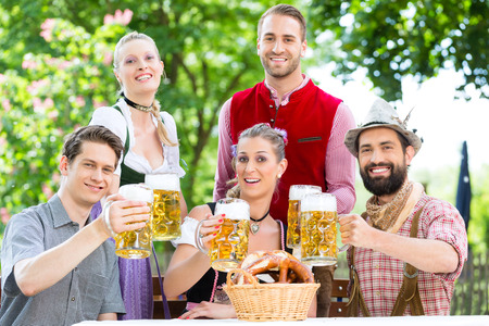 tracht: In Beer garden - friends in Tracht, Dirndl and Lederhosen drinking a fresh beer in Bavaria, Germany