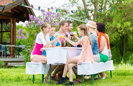 ao ar livre: Familiares e vizinhos na festa no jardim bebendo, sentando-se na frente de uma casa com amigos e família Imagens