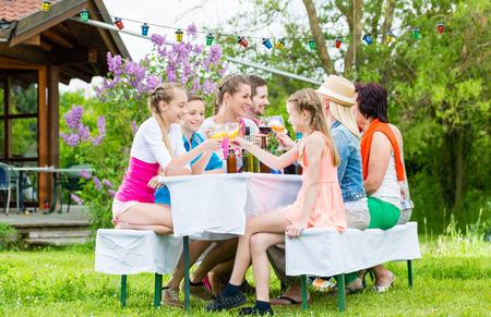 Familie en buren in de tuin partij het drinken, zitten in de voorkant van een huis met vrienden en familie
