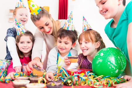 I bambini alla festa di compleanno afferrando muffin e torta, i ragazzi indossano cappelli, palloncini e bandierine di carta per la decorazione Archivio Fotografico