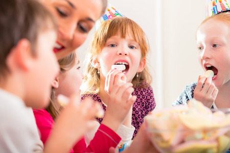 nibbling: Children on birthday party nibbling candies wearing party hats