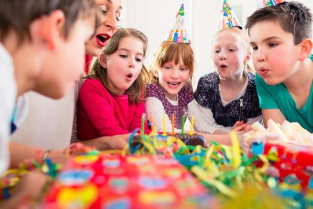 velitas de cumpleaños: Niño en la fiesta de cumpleaños soplando las velas en la torta siendo ayudado por amigos y la madre Foto de archivo